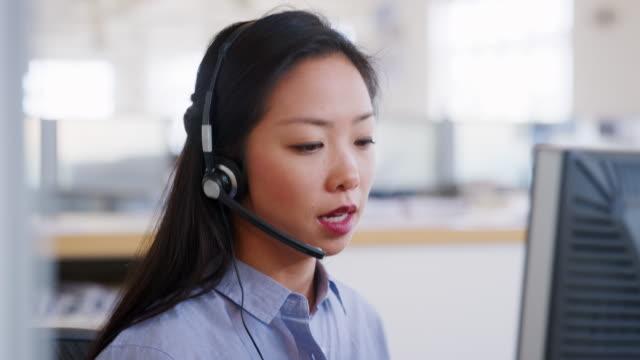 young asian woman using computer in a call centre, close up - słuchawki filmów i materiałów b-roll