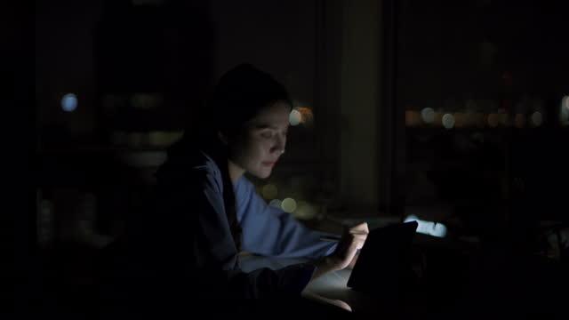 vídeos de stock, filmes e b-roll de jovem asiática usando tablet digital no quarto de cama e varanda à noite. - característica arquitetônica