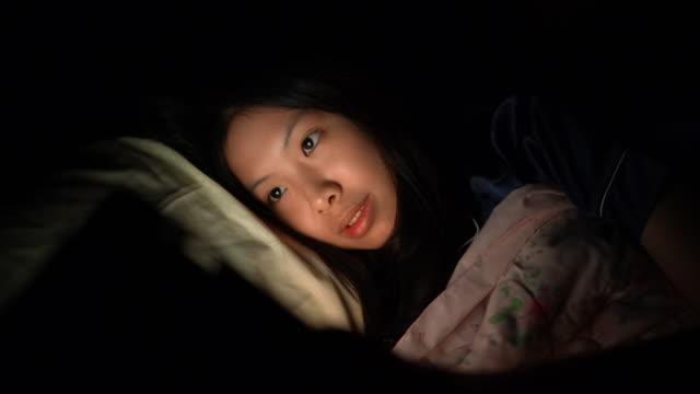 ベッドでデジタルタブレットやスマートフォンを使用して若いアジアの女性 - スマホ ベッド点の映像素材/bロール