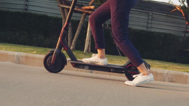 young asian woman using eco friendly vehicle - monopattino elettrico video stock e b–roll