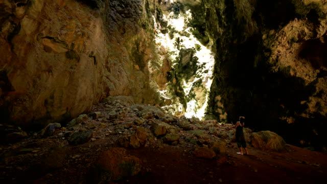 vídeos y material grabado en eventos de stock de joven asiática con pantalla táctil de teléfono móvil tomar una foto en la cueva de phraya nakorn, tailandia - letra s