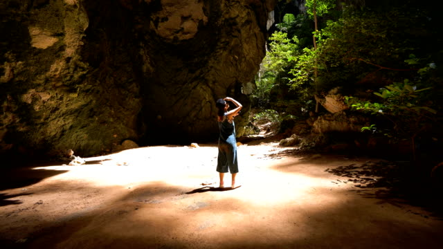 Young Asian woman using mobile phone touchscreen take a photo at Phraya Nakorn cave, Thailand Young Asian woman using mobile phone touchscreen in cave. scandal abc stock videos & royalty-free footage