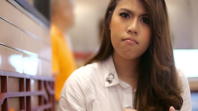 vídeos y material grabado en eventos de stock de joven asiática usando el móvil - dedo sobre labios