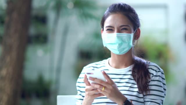 Young Asian woman using phone wear mask protect coronavirus  Young Asian woman using phone