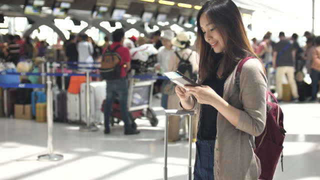 young asian woman using smart phone for check-in online - hotel checkin video stock e b–roll