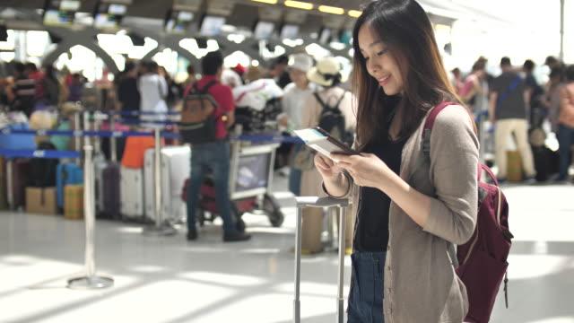 young asian woman using smart phone for check-in online - fare una prenotazione video stock e b–roll
