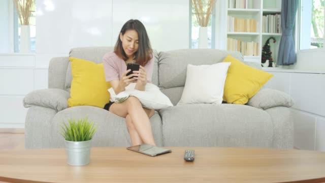 スマートフォンを利用した若いアジアの女性家庭でのリビングルームでリラックスしたときにソファの上に横たわっている間、幸せな笑顔を感じるソーシャルメディア。ライフスタイルラテ� - ソファ 女性点の映像素材/bロール