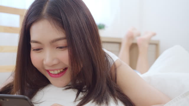 朝起きてからベッドに横たわって幸せな笑顔をソーシャルメディアチェックをする若いアジア人女性、自宅の寝室でくつろぐ美しい魅力的な日本の女の子。 - スマホ ベッド点の映像素材/bロール