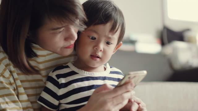 vídeos y material grabado en eventos de stock de joven asiática con smartphone en casa con su bebé - nuevo bebé