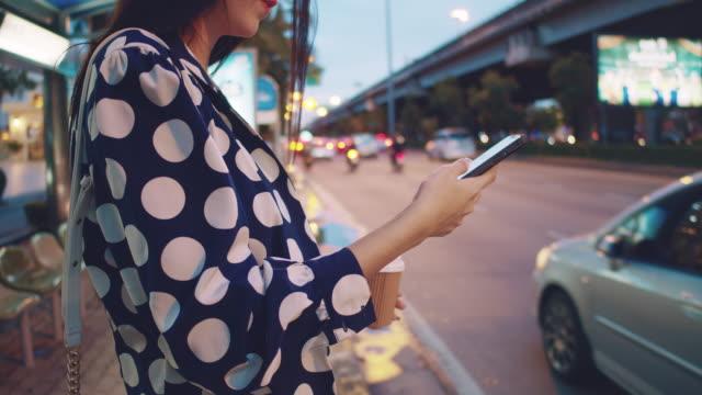 vídeos de stock e filmes b-roll de young asian woman waiting for taxi in bangkok city. - berma da estrada