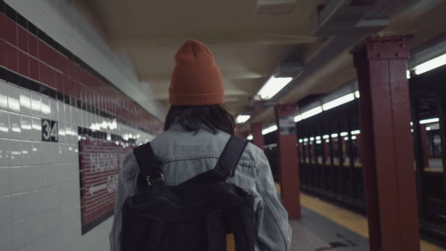 young asian woman walking on subway platform. - struttura pubblica video stock e b–roll