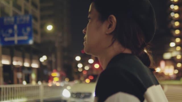 genç asya kadın yürüyüş üzerinde the sokak at gece - sadece genç bir kadın stok videoları ve detay görüntü çekimi