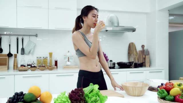 young asian woman walking to kitchen home and drinking orange juice in moring weekend day. healthy eating and healthy lifestyle concept. - disintossicazione video stock e b–roll