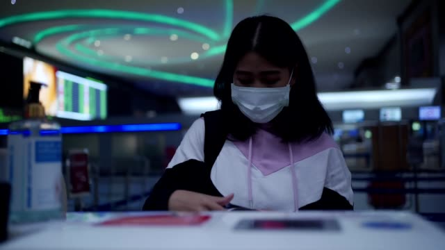 Young Asian woman wear mask receive airplane ticket from check in counter at airport terminal departure time, empty airport, covid-19 pandemic, new normal social distance, luggage check in process