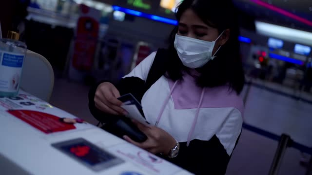 Young Asian woman wear mask receive airplane ticket from check in counter at airport terminal departure time, empty airport, covid-19 pandemic, new normal social distance, airport security check