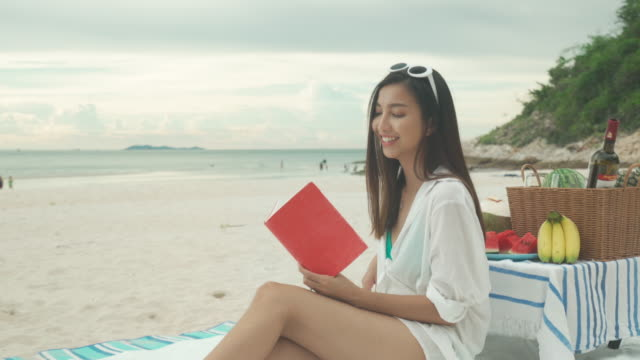 Young Asian woman wear sunglasses is relaxing with reading a book in the white sand beach and near sea with tropical fruit in background. Summer, holidays, vacation and happy people in Thailand concept.