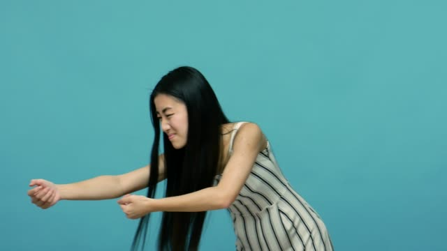 junge asiatische frau mit langen schwarzen haaren im kleid ziehen schwere unsichtbare objekt, ziehen virtuelle seil - weibliche angestellte stock-videos und b-roll-filmmaterial