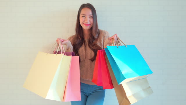彼女の手に買い物袋を持つ若いアジアの女性 - 美人点の映像素材/bロール