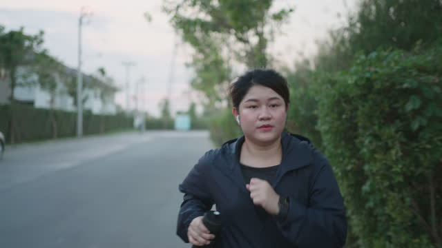 Young asian woman with wireless in-ear earphones running on road near village at sunset