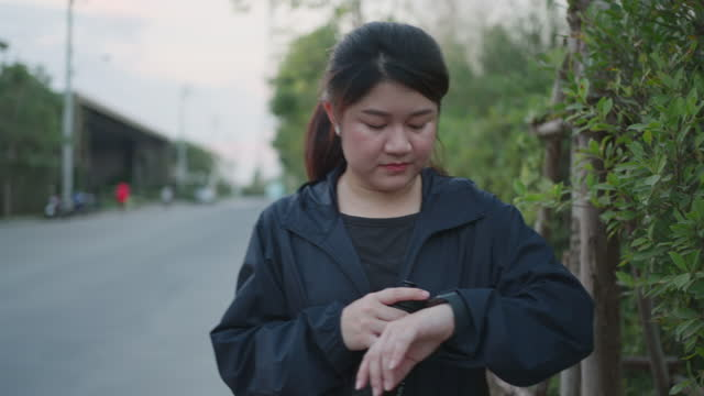 Young asian woman with wireless in-ear earphones walking on road near village at sunset