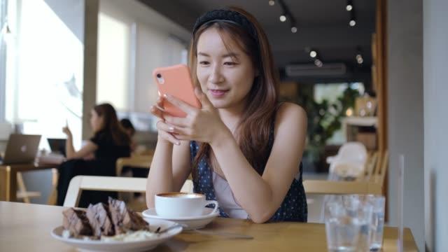 vidéos et rushes de jeune femme asiatique travaillant dans un café - 30 34 ans