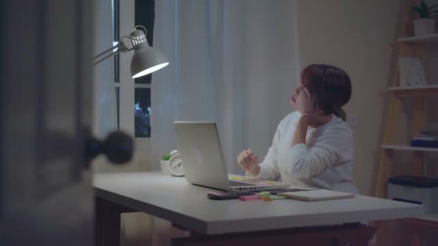 若いアジアの女性は自宅のリビングルームで机の上にノートパソコンを使用して遅く作業します。ホームオフィスで夜のノート文書ファイナンスと電卓を書くアジアビジネスウーマン。気分� - パソコン 日本人点の映像素材/bロール