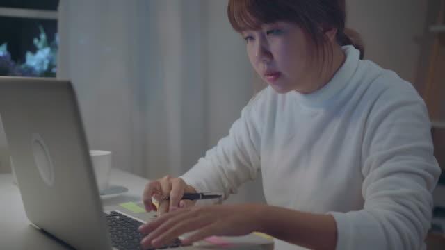 vidéos et rushes de jeune femme asiatique travaillant tard utilisant l'ordinateur portatif sur le bureau dans le salon à la maison. femme d'affaires asiatique écrivant le financement et la calculatrice de document de cahier dans la nuit au bureau à la maison. profiter du t - travailleur indépendant