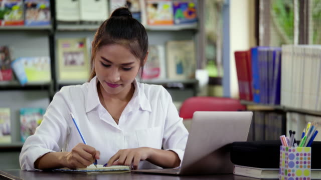 Young Asian woman writing in notebook and doing research in college library, learning education and school concept