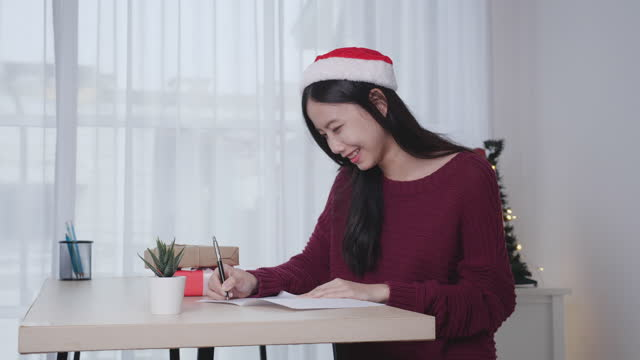 Young asian woman writing postcard in Christmas day at home, eve and celebrate, female writing message on greeting card with giving gift box, holiday and season, congratulation and celebration.