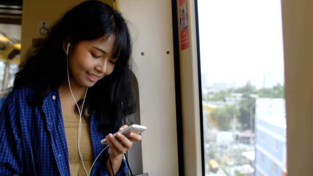 Young asian women listening to music. video