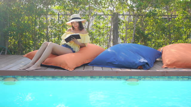 Young asian women read book around outdoor swimming pool