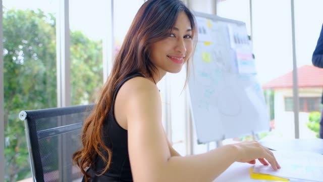 junge asiatische frauen sitzen im büro während der sitzung und drehen, um kamera und lächeln. - gutaussehend stock-videos und b-roll-filmmaterial