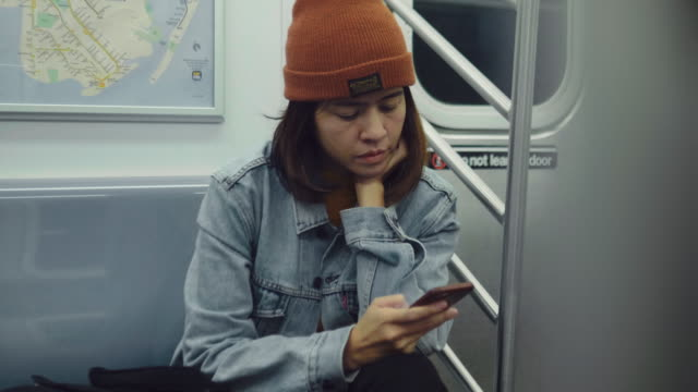 Young asian women typing message on the train. Hipster woman rides the subway at night and used smartphone. Manhattan, New York, USA new york city subway stock videos & royalty-free footage