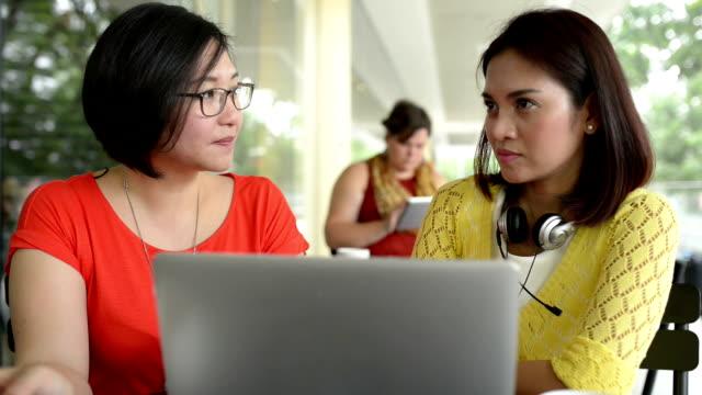 unga asiatiska kvinnor med laptop i cafe - filippinskt ursprung bildbanksvideor och videomaterial från bakom kulisserna