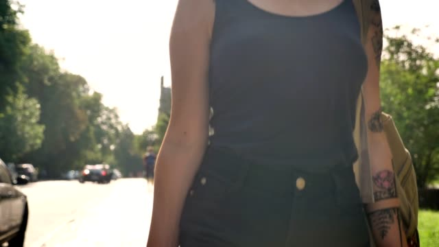 Young asian women with tattooed hand holding skateboard and backpack, walking forward in park near university Young asian women with tattooed hand holding skateboard and backpack, walking forward in park near university. sleeve stock videos & royalty-free footage