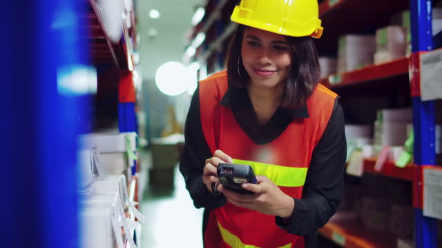 Young Asian worker woman in helmet  checking stock in warehouse inventory.