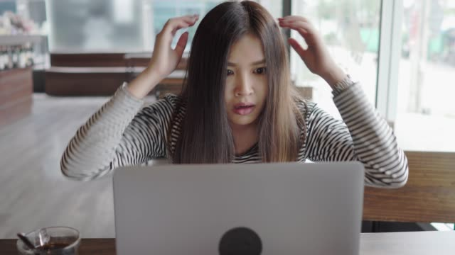 genç asyalı genç kadın şok ve kayıp laptop kafede tepki - anger stok videoları ve detay görüntü çekimi