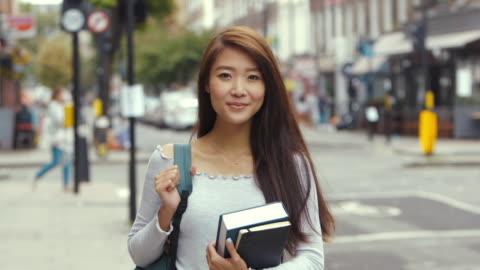 vídeos y material grabado en eventos de stock de joven aspirante a estudiante chino con libros (cámara lenta) - estudiante