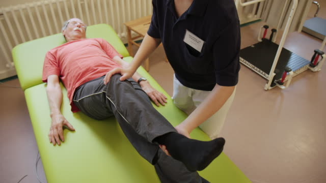 young assistant helping senior man in health club - fisioterapia video stock e b–roll