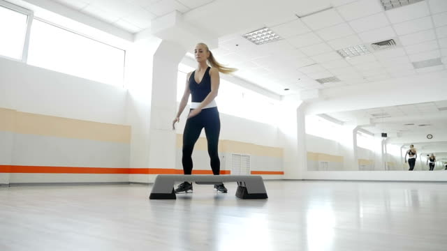 Young athlete doing basic aerobics steps in gym, slow motion video
