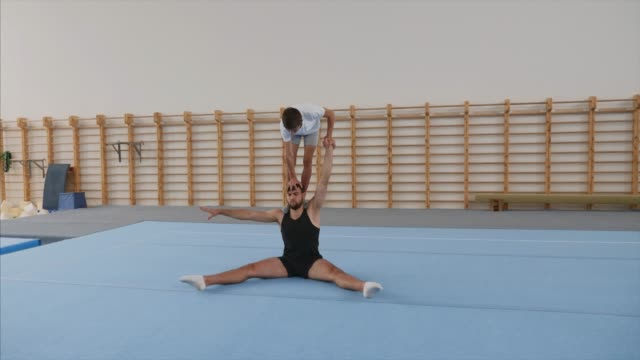 Young athlete is making handstand and front split on head of partner. Steadicam A young boy athlete is making a handstand with on hand and front split on the head of a man partner sitting in fold on the sport mat in a sport center, lands on feet. Steadicam, front view, side view. doing the splits stock videos & royalty-free footage