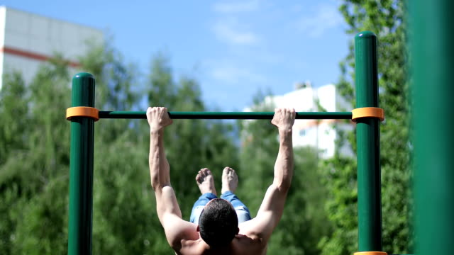 A young athlete jumps on the horizontal bar and doing a lot of flip. video