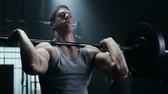 junge sportler mann und frauen, die übung mit gewichten im fitnessstudio - gewichtstraining stock-videos und b-roll-filmmaterial