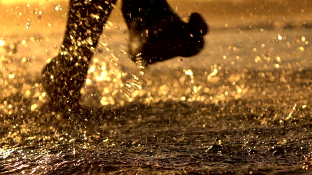 MACRO: Young athlete man running in shallow ocean, water drops sprinkling around