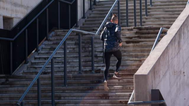Young athlete running up the stairs in an urban area video