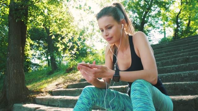 stockvideo's en b-roll-footage met jonge atleet vrouw met behulp van slimme telefoon. - blond haar