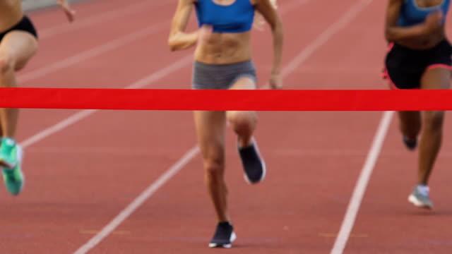 vídeos y material grabado en eventos de stock de jóvenes atletas en el estadio, cruzando la línea de llegada en cámara lenta - meta