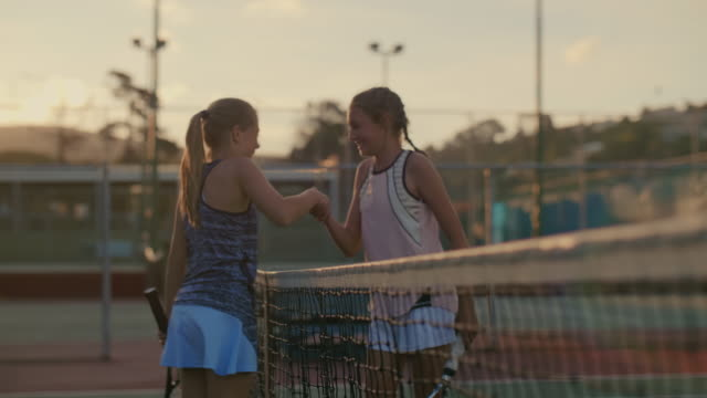 Young athletes walking up to net and shaking hands Girl tennis players shaking hands after their match tournament competition, sportsmanship spirit match sport stock videos & royalty-free footage