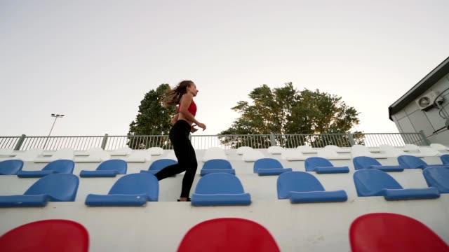 vidéos et rushes de la jeune fille athlétique fait du jogging. court le long des gradins. ralenti. plan d'ensemble. - joggeuse