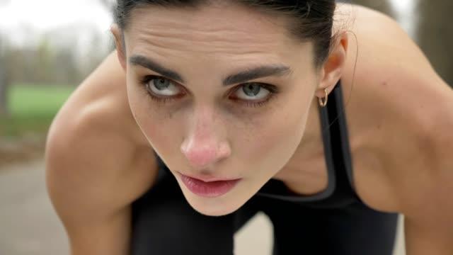 vidéos et rushes de jeune fille athlétique se prépare à courir dans le parc en été, mode de vie sain, conception de sport - commencement
